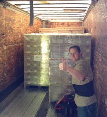 Andy unloading skids of HiTi and DNP photo supplies